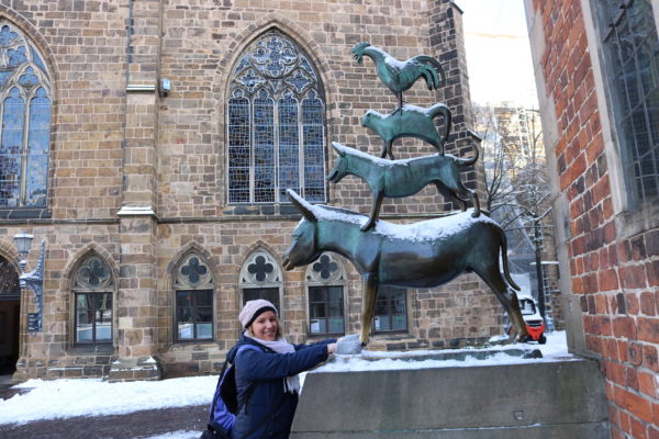 Me touching both legs of the Bremen Town Musicians' donkey for good luck